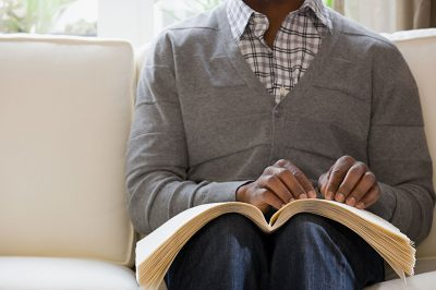 Blind man reading a braille book (Credit: XiXinXing via Shutterstock)