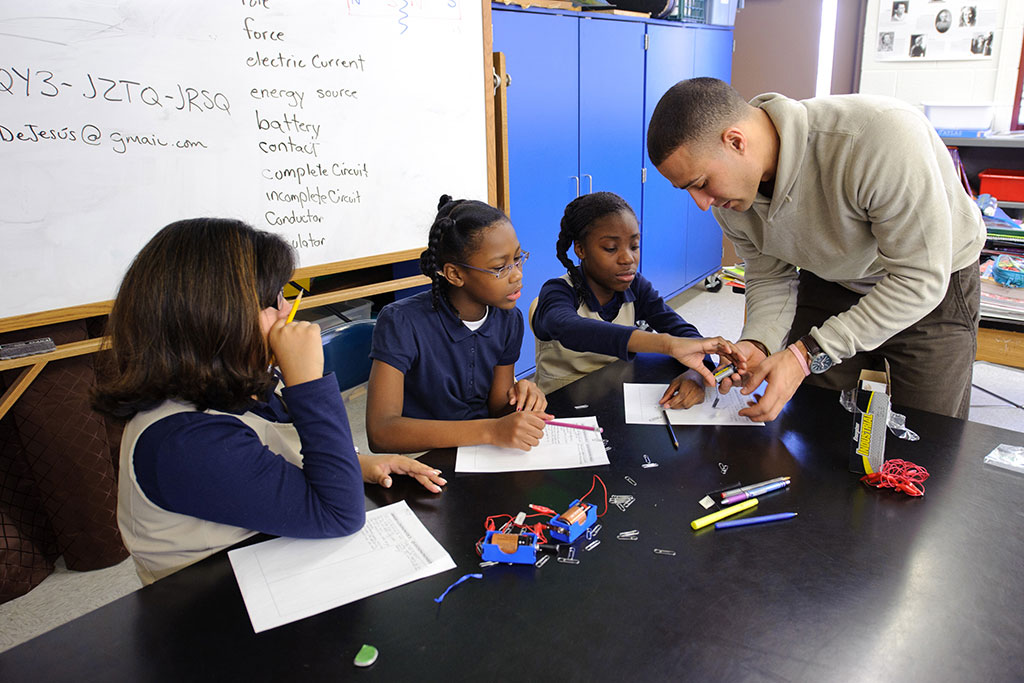 Fourth-graders working on experiment with teacher