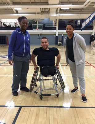 Sport management students Kenisha Lee, left, and Nadeige Bailey, right, gather with activist Ryan Martin during the Adapted Sport Wheelchair event. (UConn Recreation)