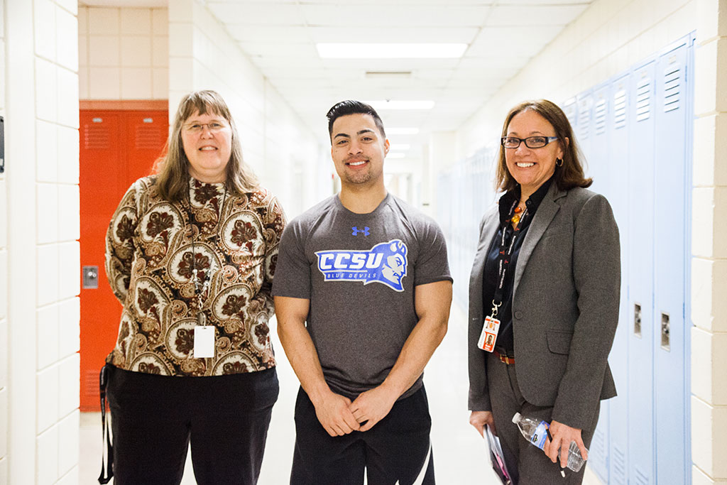 "10:45 a.m. — Teacher Wendy Fusco, pictured on the left, nominated a student, Connor Monahan, for a ""Tiger Shout Out"" for saving a life while lifeguarding at a local YMCA. Baker helps in recognizing Monahan. (Photo credit: Cat Boyce/Neag School)"
