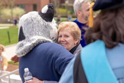 Mary Anne Doyle hugs UConn Husky Dog mascot during Commencement weekend.