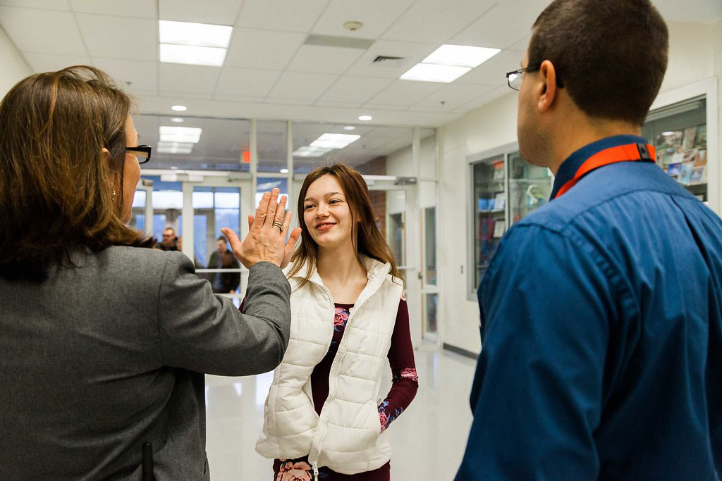 7:15 a.m. — Baker gives a high-five greeting to one of the students, as Angelo observes. She individually greets each student as they arrive, asking about their day and sharing anecdotes with Angelo. (Photo credit: Cat Boyce/Neag School)