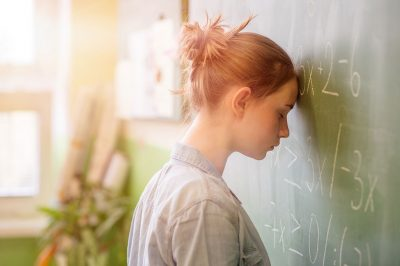 Image of student looking frustrated at a classroom blackboard (ThinkStock photo)