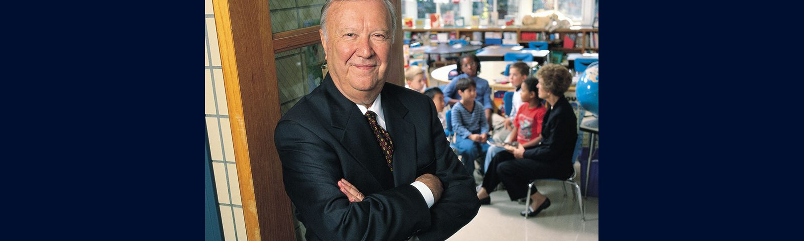 Ray Neag '56 (CLAS) stands outside of a classroom