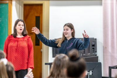 Cara Bernard, pictured on the left, looks on while Katie Cummins leads her class during the visit to UConn. (Photo credit: Frank Zappulla/Neag School)