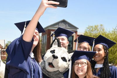 Graduate students take a selfie with Jonathan the Husky mascot at the Neag School's Commencement reception for master's and sixth-year students. (GradImages)