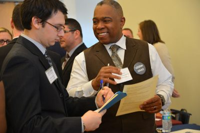 Samuel Galloway '01 6th Year, director of human resources at Bristol Public Schools, reviews a student's resume during the Education Career Fair.