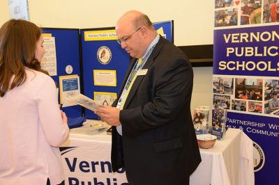 Joseph Macary '94 (ED), '08 ELP, '16 Ed.D, superintendent of Vernon Public Schools, speaks with a student during the Education Career Fair.