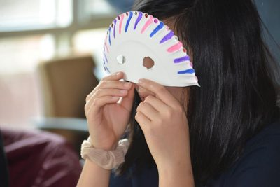A student from Ellington (Conn.) High School enjoys the mask-making session during the visit to UConn.