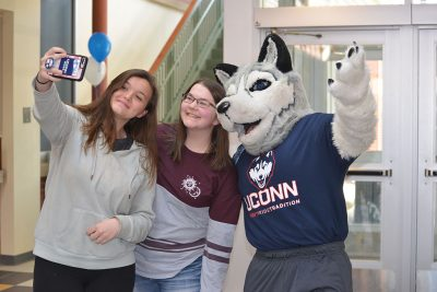 Students take a selfie with Jonathan the Husky at the Gentry Building during UConn's Giving Day in March. (Shawn Kornegay/Neag School)