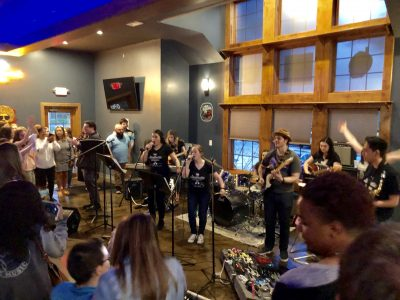 Faculty, staff, and students from the Department of Curriculum and Instruction perform at the Knot Restaurant earlier this month.