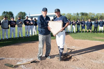 Baseball's Jim Penders '94 (CLAS), '98 MS,, right, accepts the home plate from Andy Baylock. (Stephen Slade/UConn Today)