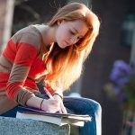 Student sitting on cement wall studying.