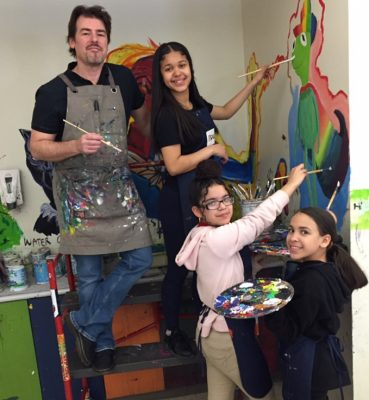 Jason Gilmore painting with his students.