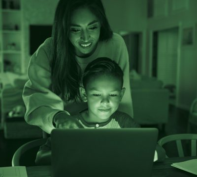 Parent overseeing child while looking at laptop,