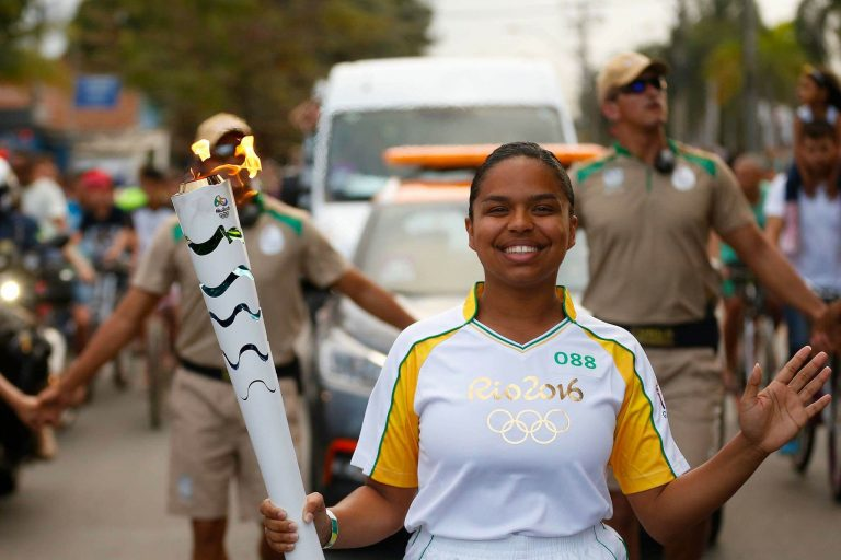 Pauline Batista holds Olympic torch in Rio at 2016 games. [Links to story on Batista.]
