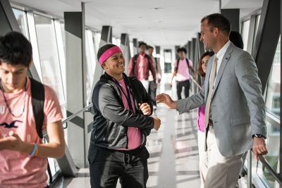 Alum and superintendent Nathan Quesnel greets a student in the East Hartford High hallway.