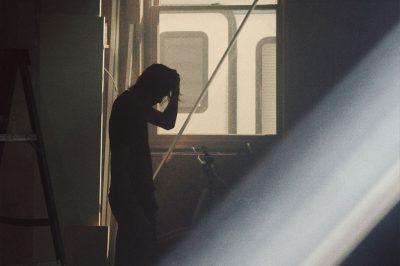 Man alone in dark hallway.