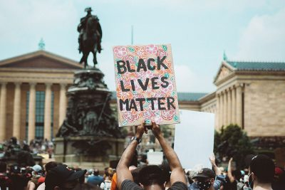 Man at Philadelphia protest holds Black Lives Matter poster.