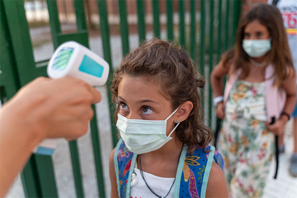 Little girl with face mask gets temp checked.