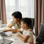 Parent and child using laptop together.