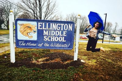 Enrique jumping up alongside the Ellington Middle School sign.