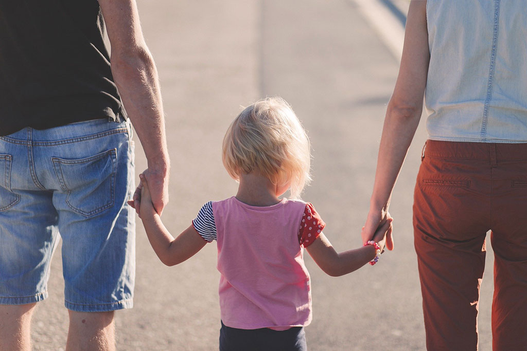 Child holding hands with two adults.