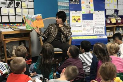 Principal Rodriguez reading a picture book to elementary school students.