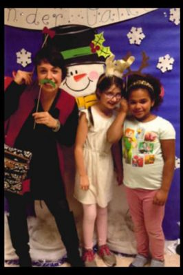 Principal Rodriguez poses with holiday props with two students.