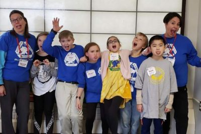 Principal Rodriguez makes funny faces with a teacher and students.