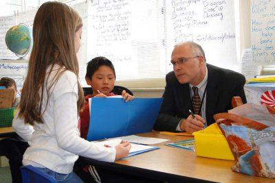Superintendent Paul Freeman listens to child read in classroom.