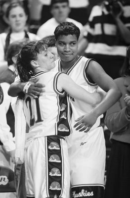 Jennifer Rizzotti and Jamelle Elliott hug on the court.