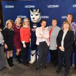 Group of women in front of UConn banner.
