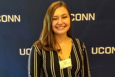 Jenna Racca smiles in front of a UConn banner.