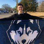 Rowan Page, Class of 2021 Neag School senior, holding UConn Husky banner.