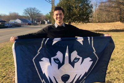 Rowan Page smiles and holds up UConn Husky banner.