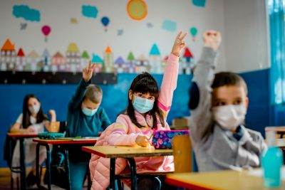 Kids wearing masks in classroom. Sandra Chafouleas says 'behavioral vaccines' can help support students' well-being.