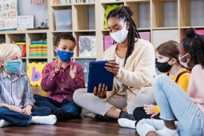 Kids and teacher wearing mask sitting on floor in classroom.