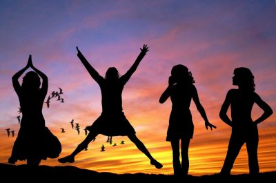 Four girls silhouetted by sunset