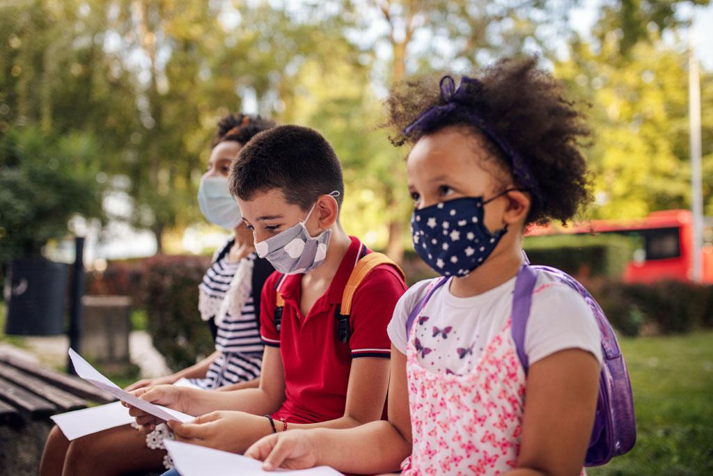 Three kids studying outside.