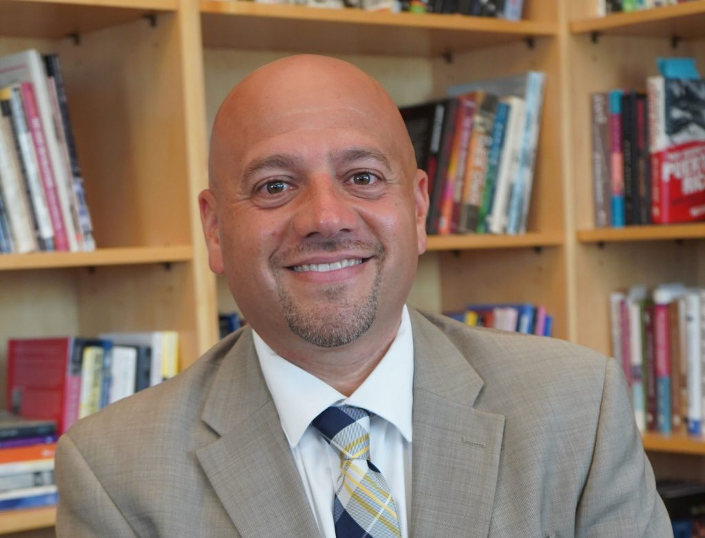 Dean Jason Irizarry sits in front of his office bookcase.