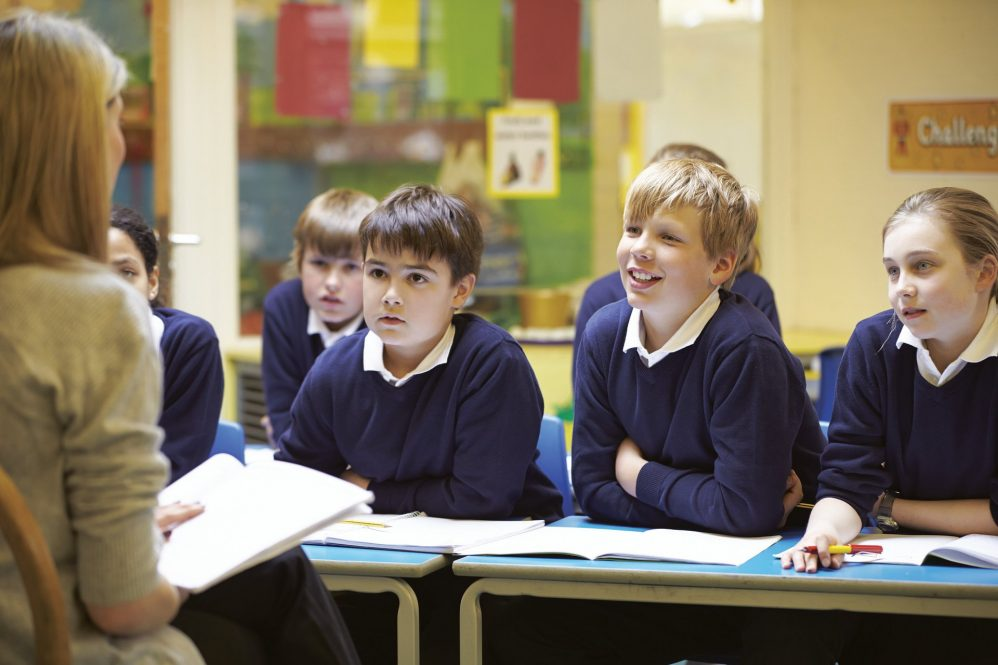 Smiling children listen to teacher during class.