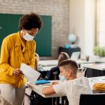 African American teacher works with school aged children, all are wearing masks.