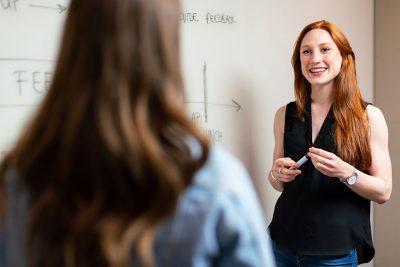 Two women talk in front of a whiteboard.