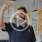 Mike Fenn holds a beaker up in the science classroom.