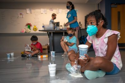 School age girl wearing mask interacts with science experiment during BRAIN Camp.