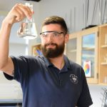 Mike Fenn in a science classroom holding a beaker.