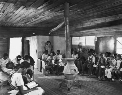 African American children sit in one-room school house around heater in a historic photo.